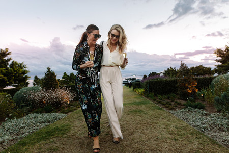 Sophisticated women walking outdoors with wine
