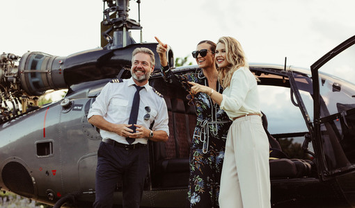 Beautiful women standing by helicopter with pilot