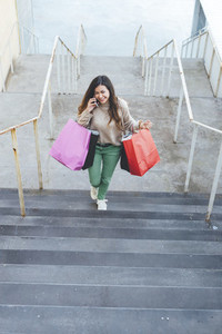 Millennial woman talking by phone with shopping bags going upstairs in shopping area
