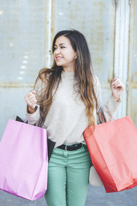 Portrait of millennial smiling woman with shopping bags in shopping area
