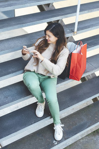 Millennial woman taking a photograph with mobile device to her shopping gifts seated in a stairs
