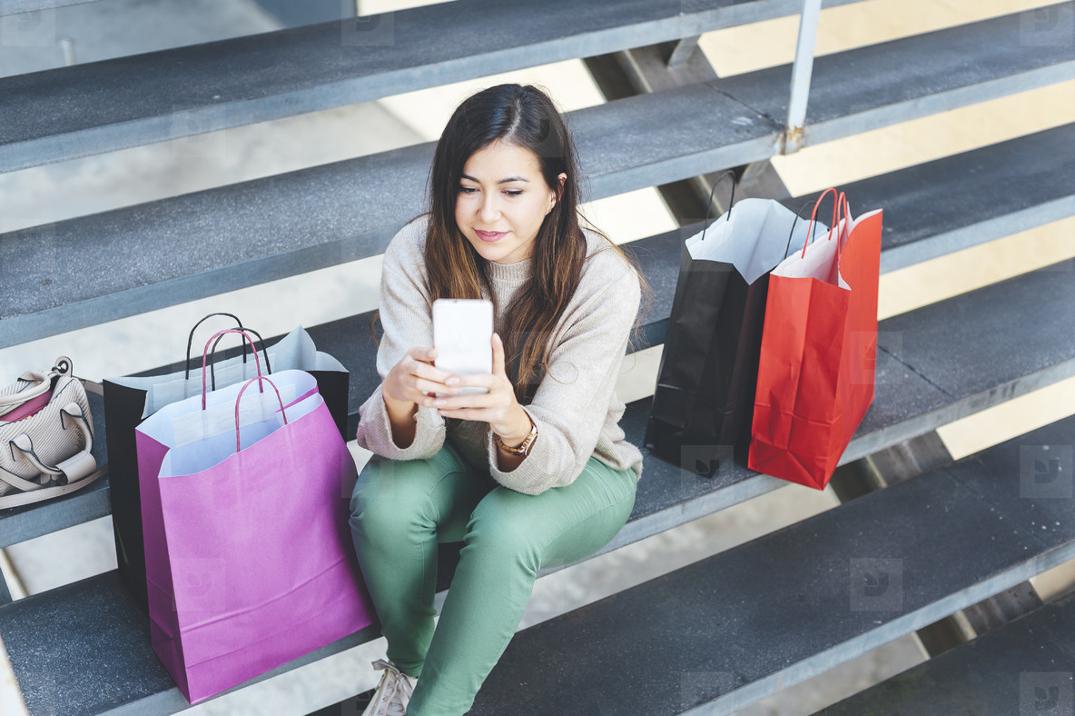Millennial woman chatting with mobile device seated in a stairs close to her shopping bags