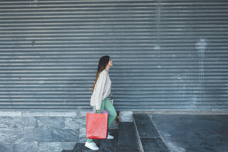 Millennial woman with shopping bags walking upstairs