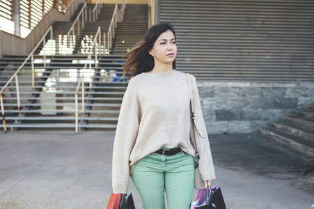 Pretty millennial woman carrying shopping bags in shopping area