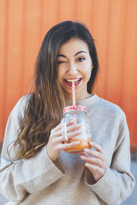 Portait of millennial woman kidding and  drinking a smoothie with orange background