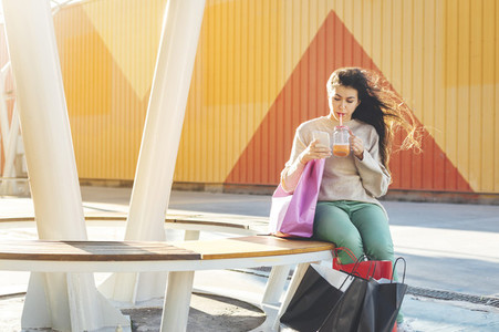 Millennial woman chatting by phone drinking a smoothie seated close to her shopping bags