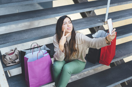 Millennial woman taking a selfie with mobile device seated in a stairs close to her shopping bags