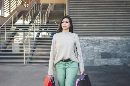 Pretty millennial woman carrying shopping bags in shopping area