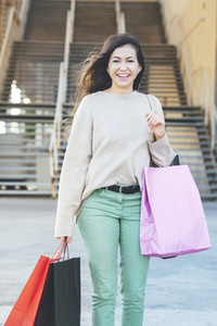 Portrait of smiling pretty millennial woman carrying shopping bags in shopping area