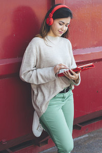 Millennial woman with red headphones using digital tablet with red background