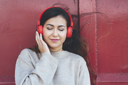 Portrait of millennial woman listening to music with red headphones in red background