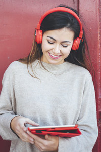 Portrait of smiling woman with red headphones using digital tablet with red background