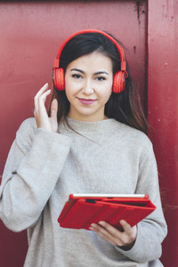 Portrait of woman looking at camera with red headphones using digital tablet with red background
