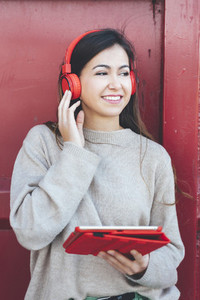 Portrait of millennial woman with red headphones using digital tablet with red background