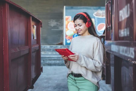 Portrait of millennial woman with red headphones using digital tablet close to a red containers