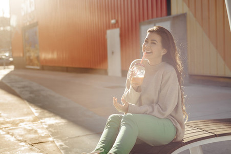 Pretty millennial woman having a break drinking a smoothie outdoors at sunset with lens flare