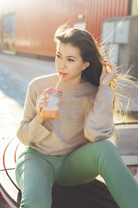 Millennial woman having a break drinking a smoothie seated close to her shopping bags