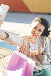 Millennial woman taking a selfie drinking a smoothie seated close to her shopping bags
