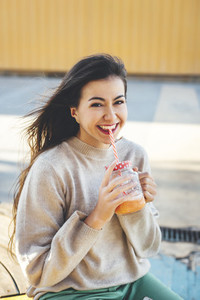 Portrait of smiling woman drinking a smoothie with yellow background