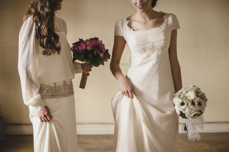 Two young brides holding her bridal bouquets