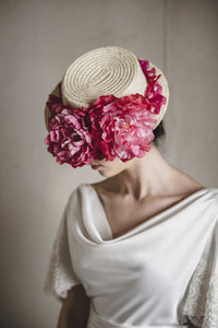 Close up of bride wearing a hat with floral arrangement