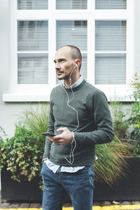 Mid aged man listening music with earphones in London streets