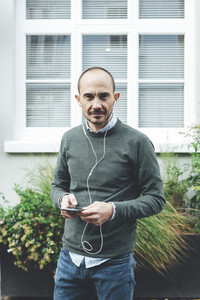 Portrait of mid aged man listening music with earphones in London streets