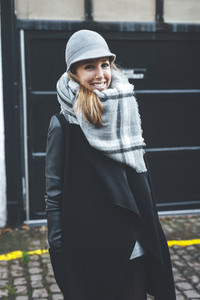 Portrait of stylish blonde smiling woman wearing grey hat and scarf in London streets