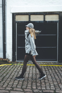 Young blonde woman wearing grey hat and scarf walks in London streets