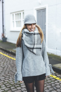 Portrait of young blonde smiling woman wearing grey hat and scarf in London streets
