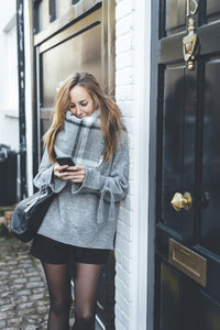 Young blonde woman chatting by mobile phone with dark handbag