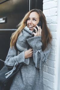 Stylish blonde woman talking by mobile phone with dark handbag