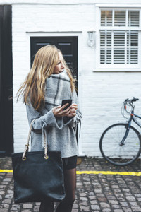 Stylish blonde woman looking away holding mobile phone and dark handbag