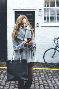 Stylish blonde woman chatting by mobile phone with dark handbag