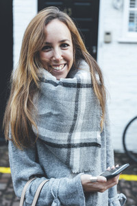 Portrait of young blonde smiling woman wearing grey scarf in London streets