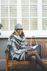 Stylish blonde woman writing with a ball pen in a notebook seated in a wooden bench with a dark handbag