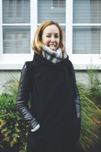 Portrait of blonde woman kidding wearing dark coat and grey scarf in London streets