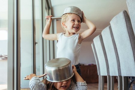 Children playing knight with kitchen utensil
