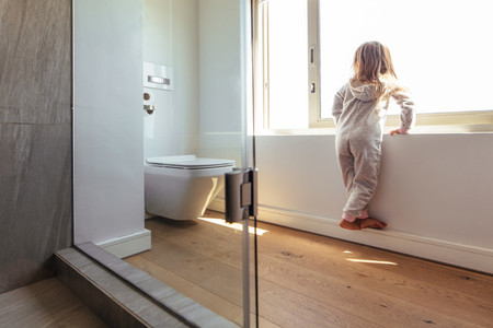 Little girl looking outside a bathroom window