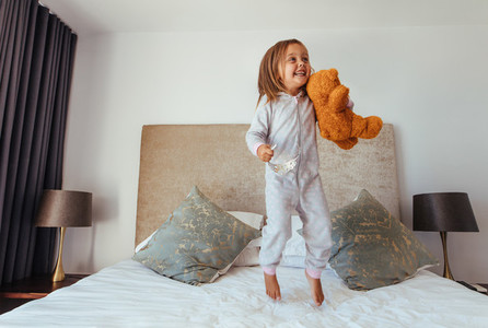 Little girl playing in bedroom