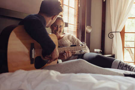 Man playing guitar for his girlfriend in bed