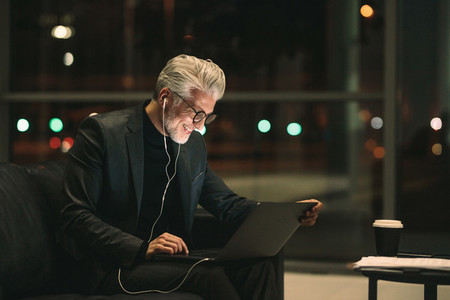 Smiling mature businessman working late on laptop