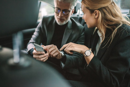 Business people using smart phone in taxi