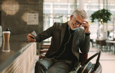 Businessman talking on phone with earphones at cafe