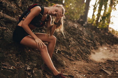 Tired woman resting by mountain trail after a run
