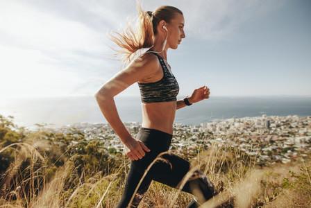 Woman training for marathon on mountain trail