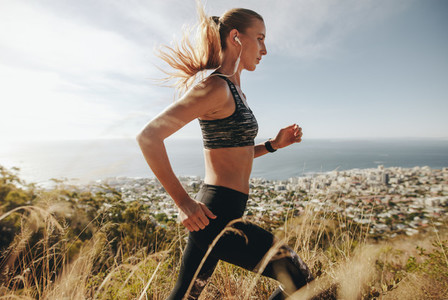 Woman training for marathon on mountain trail