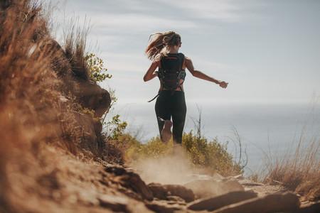 Female running over rocky trails on the hillside