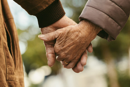Elderly couple holding hands and walking