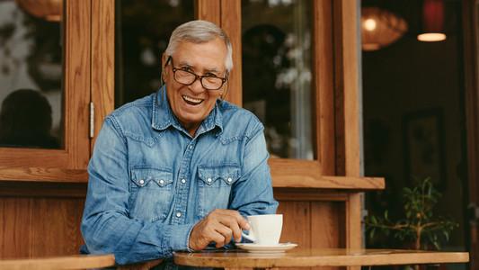 Smiling senior man relaxing at cafe